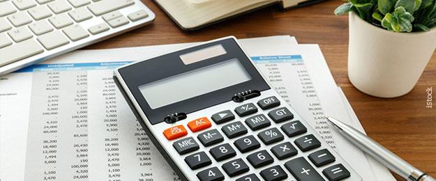 Educação financeira - Mesa com teclado de computador, calculadora, planilha, caneta e vaso de planta